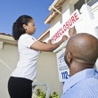 Stock Photo: Real Estate Agents Putting, For Sale, Notice Outside House