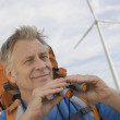 Senior Man With Binoculars At Wind Farm — Stock Photo