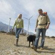 Royalty-Free Stock Photo: Senior Couple Walking With Dog Near Wind Farm
