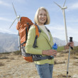 Senior Woman With Hiking Pole And Backpack At Windfarm - Foto Stock