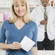 Stock Photo: WomPicking Up Prescription Drugs At Pharmacy