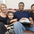 Portrait of happy family sitting on sofa - Stok fotoğraf