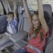Stock Photo: Cheerful children sitting at back seat of car