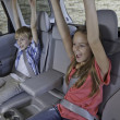 Cheerful children sitting at the back seat of car - Stockfoto