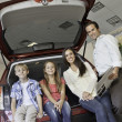 Portrait of happy family sitting at back of their new car — Stock Photo #21871511