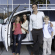 Happy family next to white car — Stock Photo