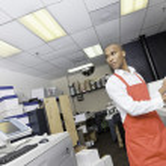 African American man working at printing press — Stock Photo