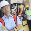 Portrait of a man in front of two workers — Stock Photo
