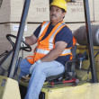 Forklift driver driving in warehouse — Stock Photo