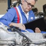 Senior mechanic analyzing car engine and holding clipboard — Stock Photo