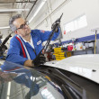Senior mechanic working on windshield wipers — Stockfoto
