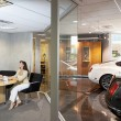 Woman sitting in car showroom office — Stock Photo