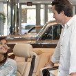 Couple checking out new cars in dealership showroom — Stock Photo