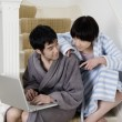 Young couple in bathrobe sitting on stairway with laptop — Stock Photo