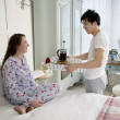 Man bringing wife breakfast in bed — Stock Photo