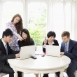 Stock Photo: Businesspeople working on laptop