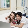 Young happy couple sharing laptop on sofa — Foto de Stock