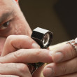 Close up of man looking at jewelry through magnifying glass — Stock Photo #21873891