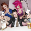 Stock Photo: Mholding two playing cards with erotic females sitting besides him