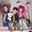 Stock Photo: Handsome guy holding playing cards with tattooed women sitting besides