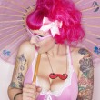 Stock Photo: Side view of tattooed womholding parasol