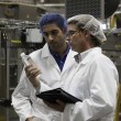Factory workers inspecting bottled water at bottling plant — Stock Photo
