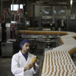 Stock Photo: Worker inspecting orange juice bottle at bottling plant