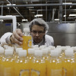 Quality control worker checking juice bottle on production line — Foto de stock #21874883