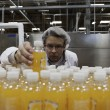 Stockfoto: Quality control worker checking juice bottle on production line