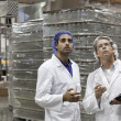 Quality control workers inspecting at bottling plant - Stock Photo