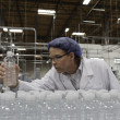 Stockfoto: Quality control worker checking bottled water at bottling plant