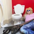 Man lying down in toilet with a guitar — Stock Photo