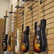 Five electric guitars hanging on display rack in store for sale — Stock Photo #21876111