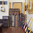 Electric guitars with guitar cases and amplifier in store — Stock Photo