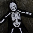 Boy dressed up as skeleton posing on rock — 图库照片