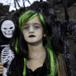 Foto de Stock  : Portrait of girl dressed up as witch while her friends dressed up in skeleton costume
