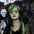 Portrait of girl dressed up as witch while her friends dressed up in skeleton costume - Stock Photo