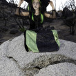 Little young girl costumed as witch sitting on rock looking away — Stock Photo #21876319