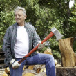 Stock Photo: Senior lumber jack holding axe and looking away