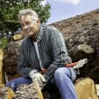 Stock Photo: Senior msitting on wood logs with axe