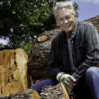 Smiling senior man sitting on logs — Stockfoto