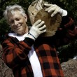 Stock Photo: Senior mcarrying firewood over his shoulders