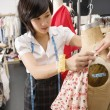 Stock Photo: Female fashion designer pinning costume on mannequin