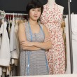 Young fashion designer with arms crossed standing next to a mannequin — Stock Photo
