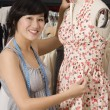 Young fashion designer adjusting dress on the dummy — Stock Photo