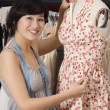 Young fashion designer adjusting dress on the dummy — Foto de Stock