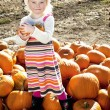 Portrait of a young girl standing on pumpkin — Stock Photo
