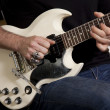 Close-up of mid adult man&#039;s torso playing guitar - Stock Photo