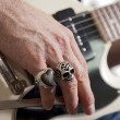 Close-up of mid adult man&#039;s fingers with rings playing guitar -  