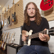 Portrait of serious mid adult man sitting in guitar store — Stock Photo